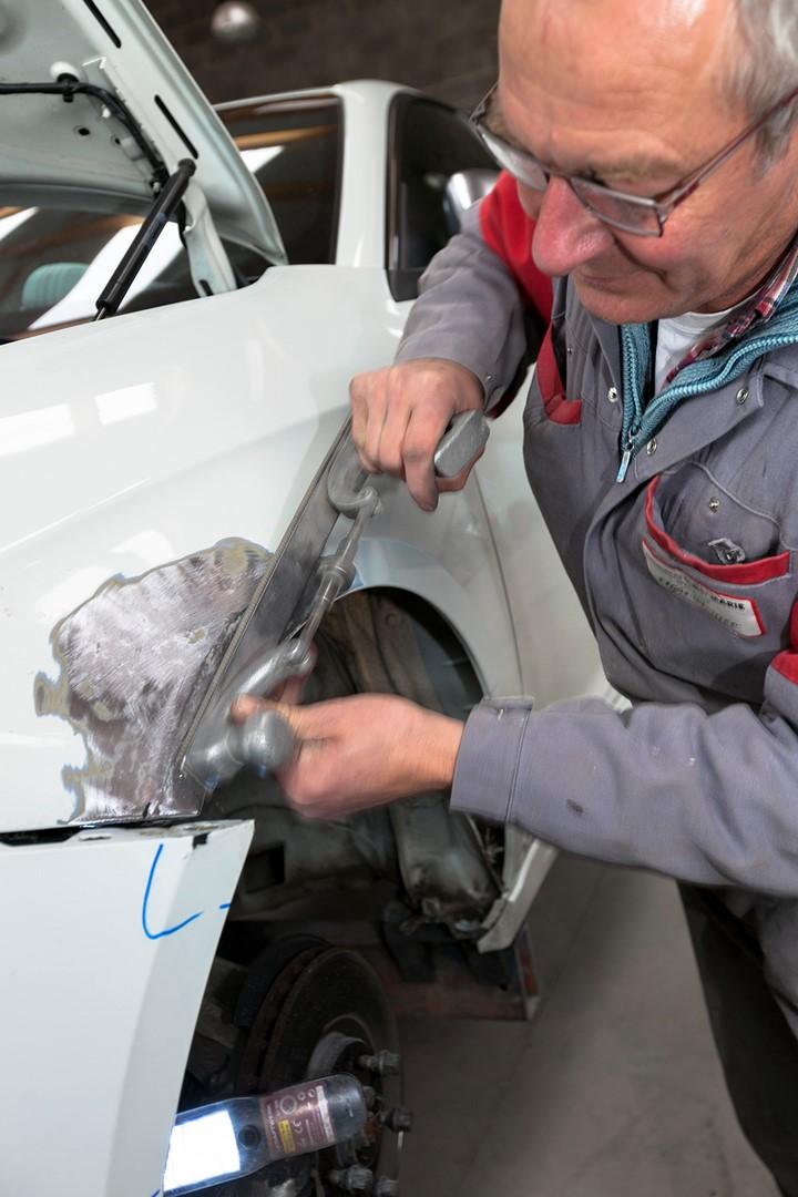 Un carrossier en train de redresser un véhicule - Entretien, réparation et carrosserie